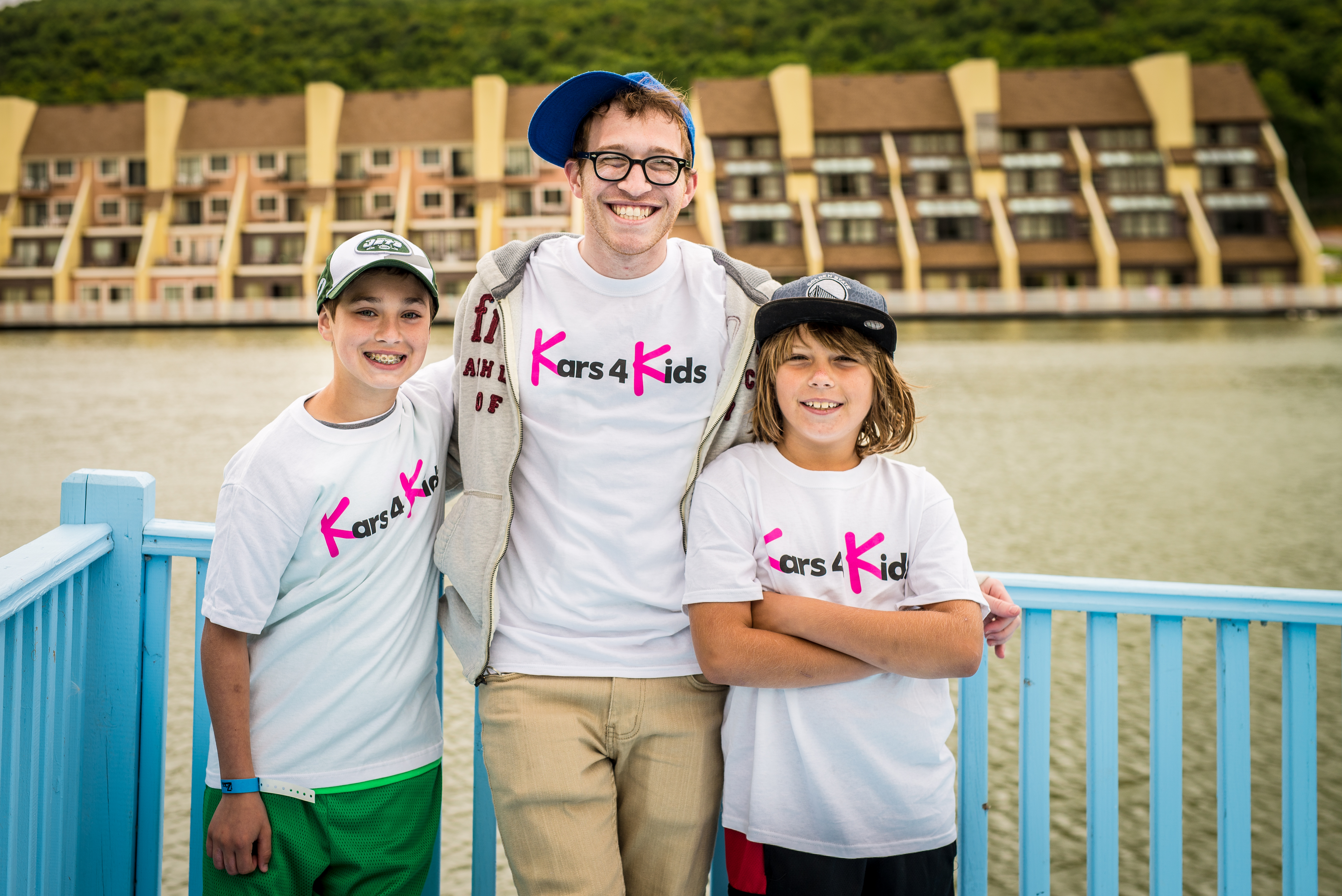 an adult and 2 children smiling and wearing kars4kids t shirts