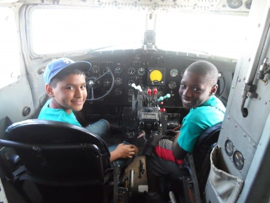 Two smiling boys, one Latino, one black, sit in the cockpit of a plane