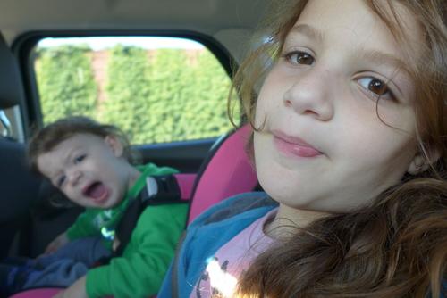 Smug little girl after torturing sibling in backseat of car