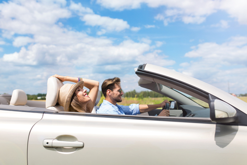 convertible car with the top down, driver and passenger enjoy the air and sun
