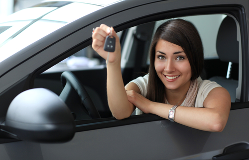 woman driver happy to be holding car keys while inside her car