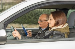 Adult female takes driving test with elderly tester, wearing glasses, in passenger seat with clipboard and pen
