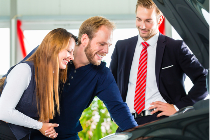 smiling couple with car and smiling car salesman