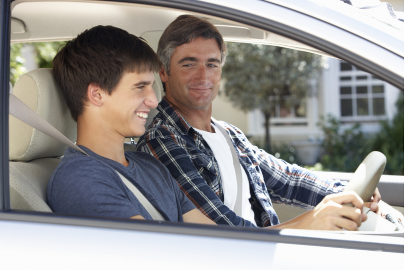 father teaching teenage son how to drive