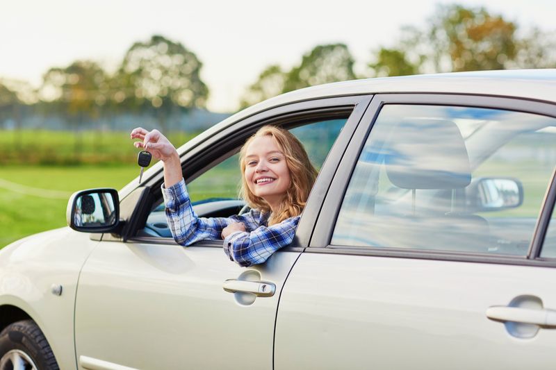 smiling teenage girl finally ready to drive at wheel holds keys out window