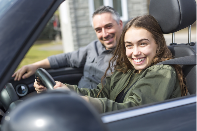 smiling teenage girl learning to drive smiling instructor