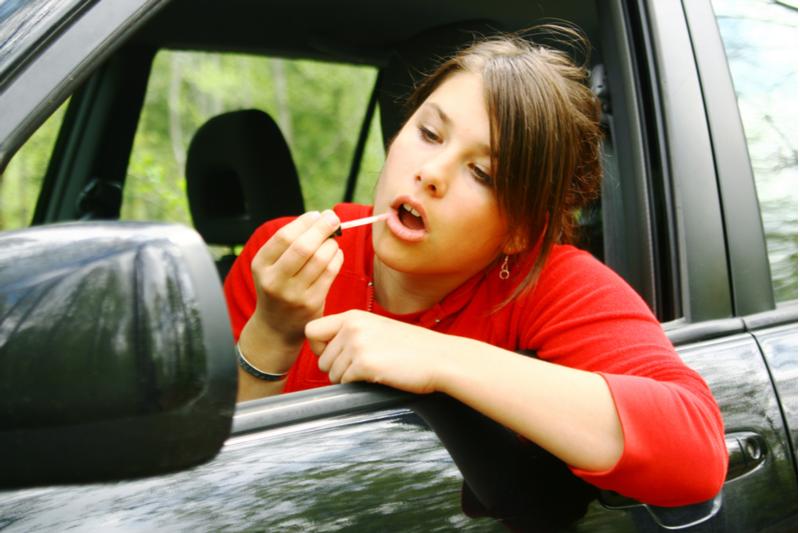 teenage girl applying lip gloss distracted driving
