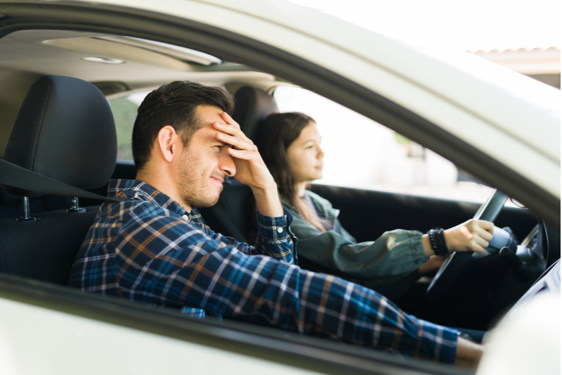 teenage girl driving as patient grinning father places hand on his forehead