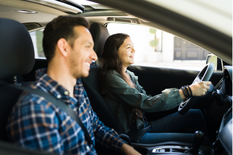 teenage girl practices driving with dad